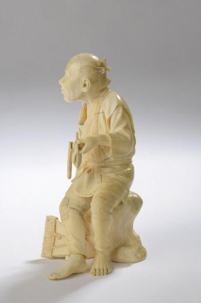 Okimono en ivoire, bûcheron ou homme assis sur un rocher, fumant la pipe, une hache...
