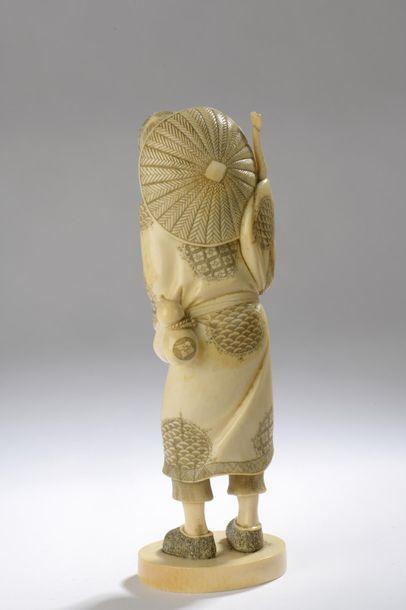 Okimono en ivoire, vieil homme debout, un bâton noueux dans la main droite, son...