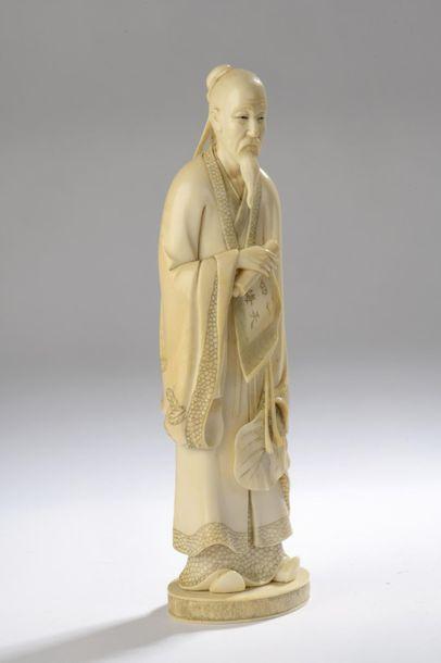 Okimono en ivoire, lettré chinois debout, un rouleau dans la main droite, un éventail...
