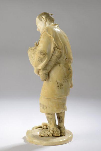 Okimono en ivoire, paysan debout, un panier de champignons sous le bras, deux champignons...
