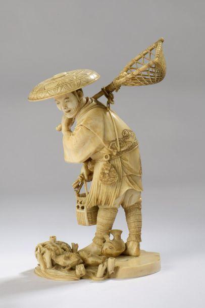 Okimono en ivoire, pêcheur debout, son filet dans le dos, des poissons à ses pieds....