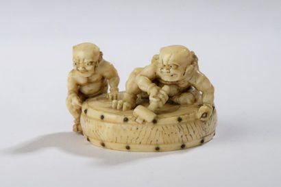 Netsuke en ivoire, deux onis juchés sur un...