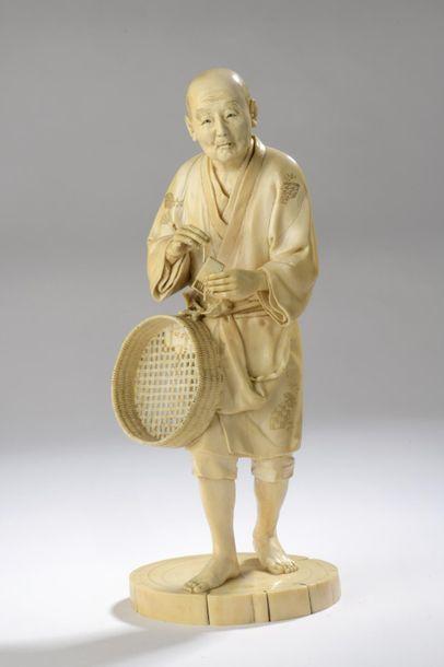Okimono en ivoire, personnage debout, une boîte d'allumettes dans la main gauche,...