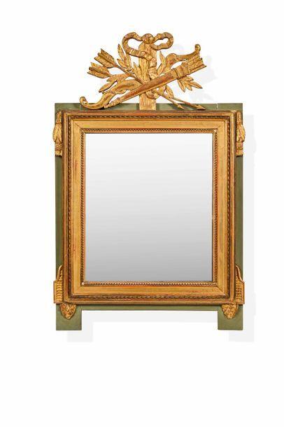 Miroir en bois doré surmonté d'un motif de...