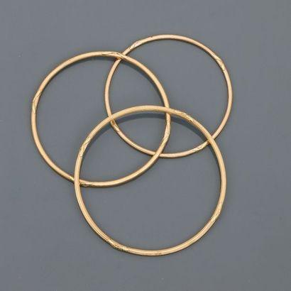 Trois bracelet jonc à décor de rubans croisés...