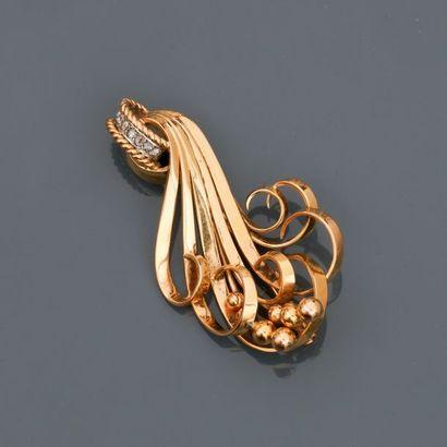Broche à décor d'enroulements d'or jaune,...