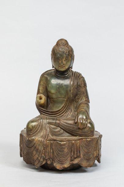 Buddha assis sur une base couverte du textile...