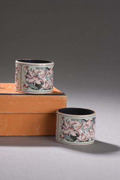 HERMÈS. Paire de ronds de serviette en métal laqué à décor de lotus sur fond céladon....