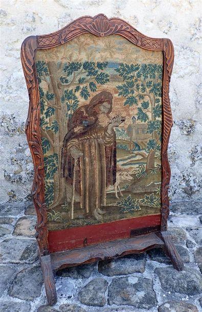 Ecran de cheminée en noyer, à décor de coquilles et feuilles d'acanthe. Tapisserie au petit point représentant Saint-Antoine. Travail régional, XVIIIème. Accidents. H: 104,5 cm. L: 62 cm.