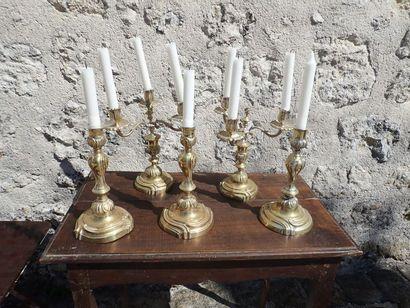 Lot de flambeauxcomprenant: Une paire de bouts de table en laiton à trois bras de lumières. Une paire de flambeaux en laiton et un faisant suite.