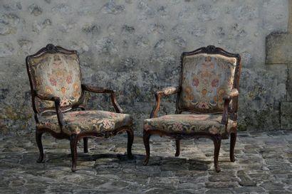 Paire de fauteuils en noyer à décor de coquille et fleur, à accotoirs à feuilles d'acanthe. XVIIIème siècle. Belle Garniture dans le goût du XVIIIème à décor de pots de fleurs. Accidents et restauration et renforts. H: 97,5 cm. L: 68 cm P: 55cm