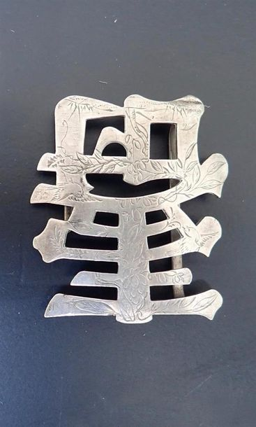 Une boucle de ceinture en forme d'idéogramme...