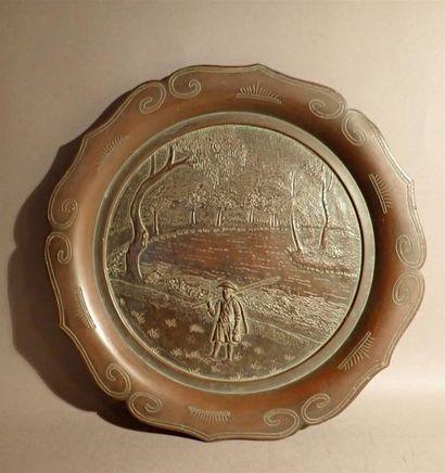 Assiette en bronze à décor ciselé d'un pêcheur...