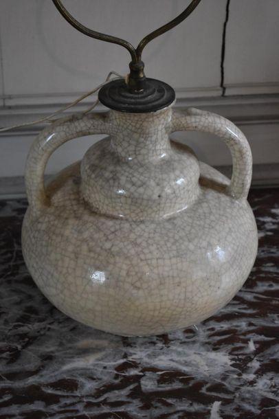 LAMPE, vers 1930 En céramique à fond ivoire....