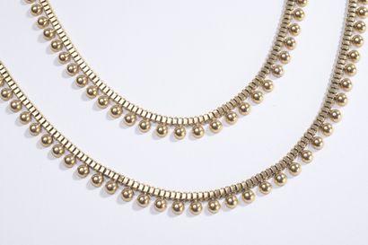 Deux colliers en or ornés d'un rang de demi-boules....