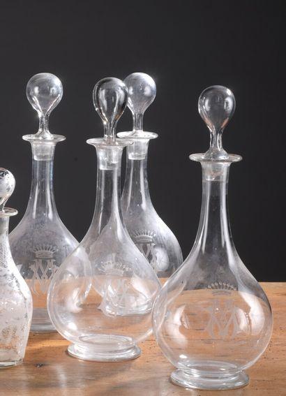 Quatre carafes et leurs bouchons en cristal à décor gravé sur la panse d'un chiffre...