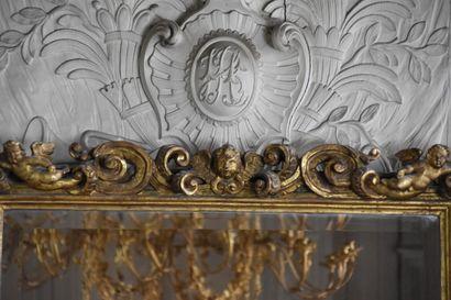 Glace en bois mouluré, sculpté et doré, Italie XVIIe siècle  A riche décor de putti...