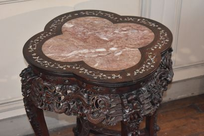CHINA, early 20th century  A richly carved blackened wood pedestal table with marble...