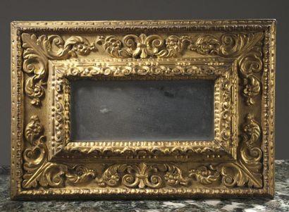 Glace en bois mouluré et doré à décor feuillagé,...