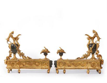 Paire de chenets en bronze patiné et bronze doré à décor d'aiguière et bouc, trophées...