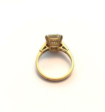 Bague en or jaune 750 millièmes, ornée d'un diamant octogonal entre deux diamants...