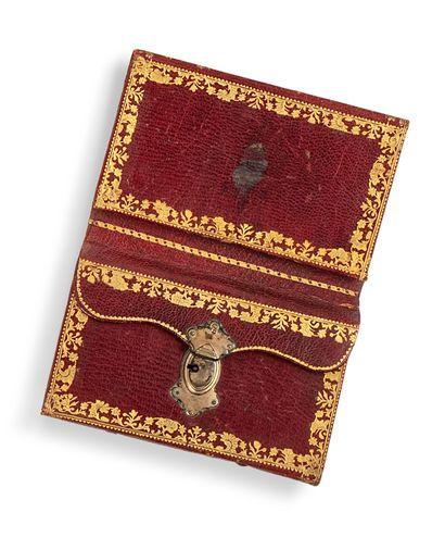 Petit portefeuille en maroquin rouge, doré aux fers à décor de fleurs et de feuil-lages ; petite serrure en laiton doré ; il contient un petit calendrier pour l'année 1772 ; 80 x 127 mm.