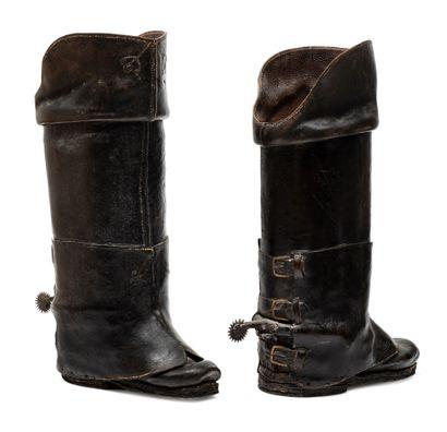 Paire de bottes de postillon en cuir fort, noir, verni, orné de coutures et d'un petit décor de cloutage en fer ; intérieur molletonné ; elles sont présentées avec leurs éperons en fer maintenus par une forte pièce en cuir en forme de guêtre fixée à l'arr