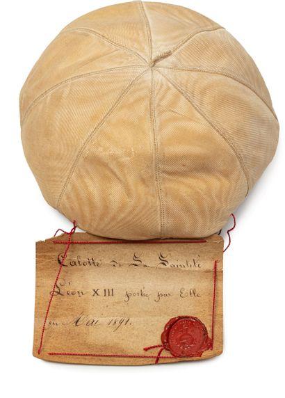 Calotte de Sa Sainteté Léon XIII, donnée en mai 1891 avec le cachet de cire rouge du Vatican. Elle est en peau de chamois, garnie de satin blanc.