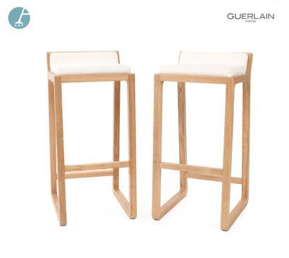 Deux tabourets hauts, piètement bois naturel et revêtement de cuir beige.  Marque...
