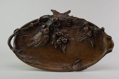 ECOLE début XXe. Plat ovale en bronze à décor d'oiseau se bécotant et de cerises....