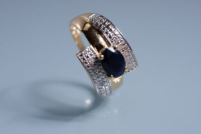 RING in 18 ct yellow gold set with a dark oval sapphire of about 1 ct framed by...