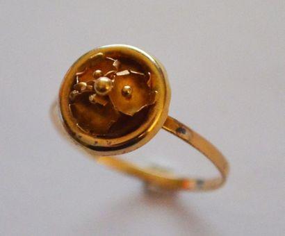 BAGUE en or ornée d'une fleur dans un cercle....