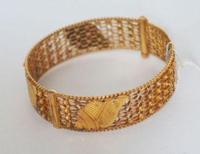 BRACELET rigide articulé en or ajouré à décor...