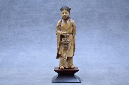 CHINE. Femme au panier en ivoire sculpté,...