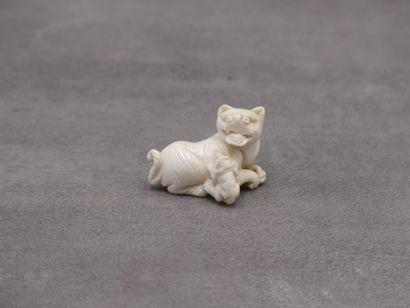 Netsuke en ivoire figurant un chien de Fo....