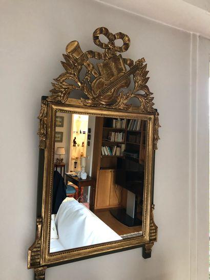 Miroir en bois et stuc doré, le fronton au...