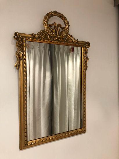 Miroir en bois doré, le fronton orné d'une...