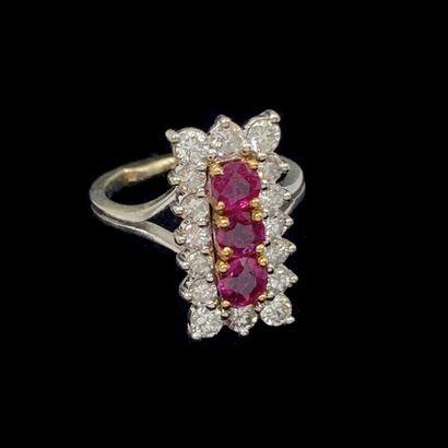 BAGUE rectangulaire en or gris (750‰) serti de trois rubis, entourés de seize diamants...