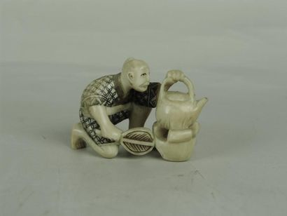 NETSUKE EN IVOIRE. Représentant un servant préparant du thé. (Signature dans cartouche)....