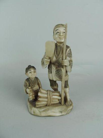 OKIMONO EN IVOIRE. Représentant un paysan au fagot avec un enfant. (Signature dans...