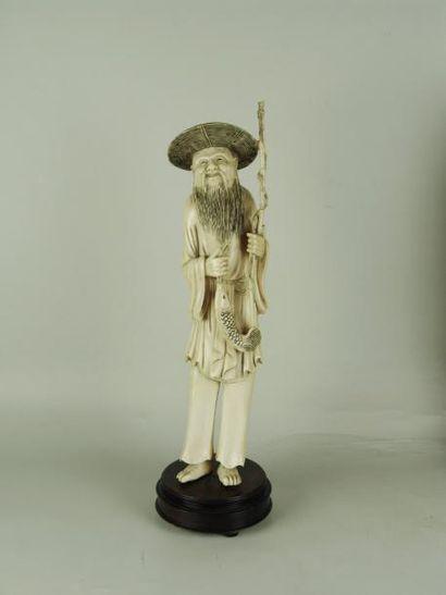 PÊCHEUR EN IVOIRE. Représenté debout sur un socle en bois, à la longue barbe, portant...