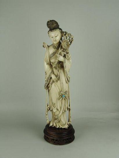 JEUNE FEMME EN IVOIRE. Représentée debout sur un socle en bois. Elle tient une branche...