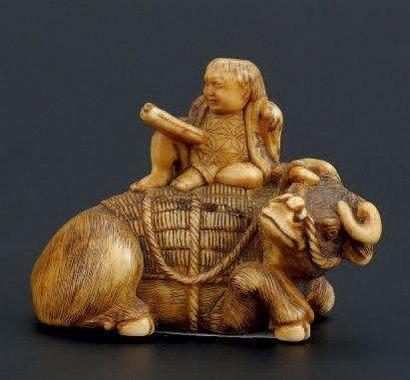 NETSUKE en ivoire représentant un enfant lisant sur un buffle.signature. Japon XIXème...