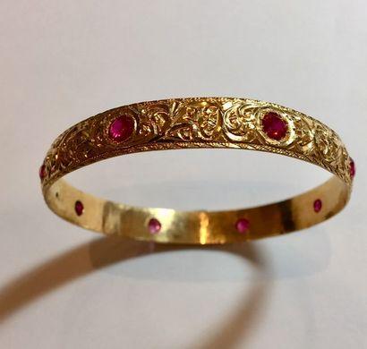 BRACELET rigide en or jaune (750 millièmes) ciselé de volutes, serti de pierres...