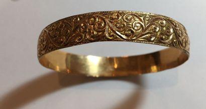 Large BRACELET jonc en or jaune (750 millièmes) guilloché et ciselé de volutes....