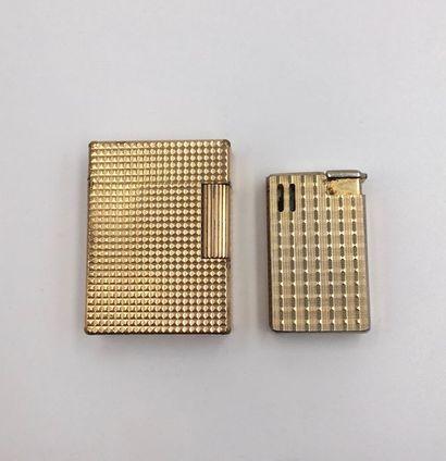 Deux BRIQUETS en métal doré guilloché à motifs...