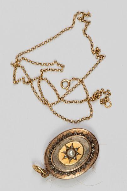 Un médaillon en argent avec chaîne en or,...