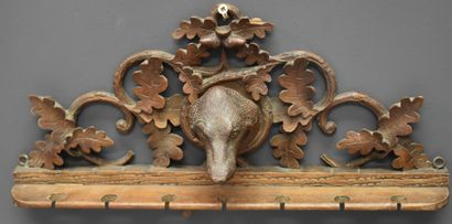 A hunting pipe holder. Black Forest work, late 19th century. Carved with a dog's...