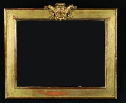 Miroir avec cadre en bois doré à décor d'écusson....