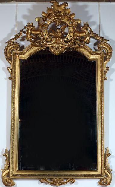 Grand miroir en bois doré à décor de frise...